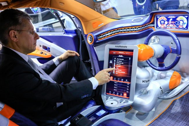 A worker demonstrates the Harman International Industries Inc. Rinspeed Budii concept car at the Mobile World Congress in Barcelona, Spain, on Monday, Feb. 22, 2016. Mobile World Congress, an annual phone-industry event organized by GSMA Ltd., runs from Feb 22 to Feb 25. Photographer: Pau Barrena/Bloomberg via Getty Images